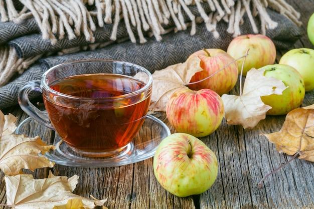Gorąca herbata z jabłkami i ciastem na stole