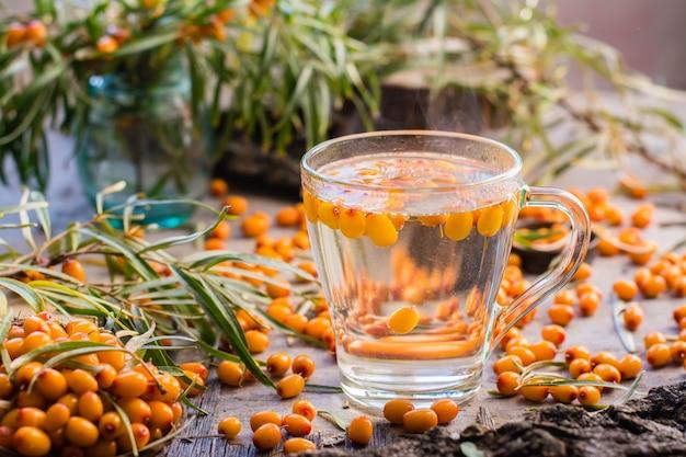 Gorąca herbata z jagodami rokitnika w szklance