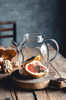 Gorąca herbata z kawałkami świeżego grejpfruta na podłoże drewniane. napój zdrowy, eko, wegański