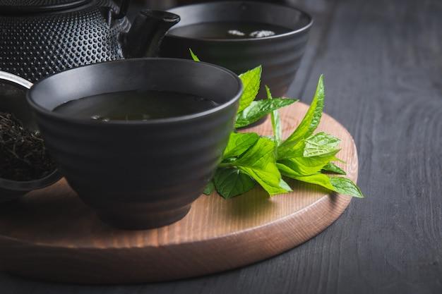 Gorąca herbata z miętą w czarnej filiżance na ciemnym tle. chińska herbata.