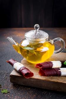 Gorąca herbata z miętą w imbryku i rolce ze skórki suszonych owoców