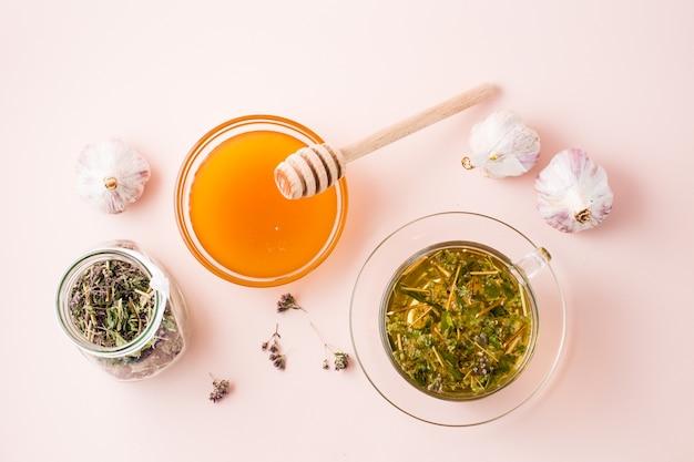 Gorąca herbata z oregano w filiżance, miód w misce, główki czosnku i suszone ziele w słoiku. ziołolecznictwo i terapia alternatywna. widok z góry