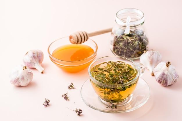 Gorąca herbata z oregano w filiżance, miód w misce, główki czosnku i suszone ziele w słoiku. ziołolecznictwo i terapia alternatywna