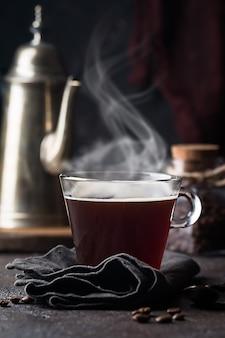 Gorąca kawa espresso z dymem w przezroczystej szklanej filiżance na czarnej powierzchni