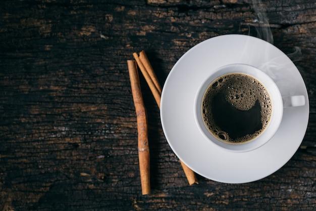 Gorąca kawa, filiżanka kawy espresso cynamonowa kawa na drewnianym stole