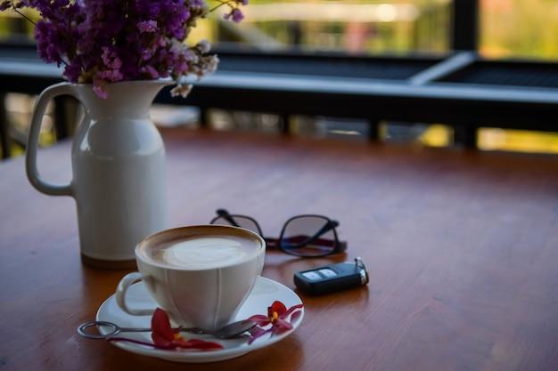 Gorąca kawa, gotowa do wypicia w filiżance kawy, umieszczona obok wazonu na kwiaty