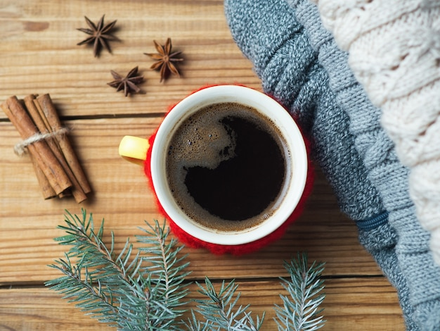 Gorąca kawa i przytulne tło do domu. ciepłe swetry z dzianiny, gałązki choinkowe i laski cynamonu