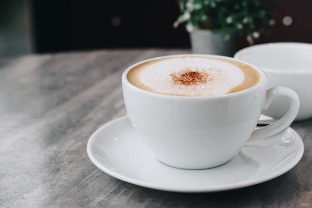 Gorąca kawa i wazon z zielonymi liśćmi na marmurowym stole