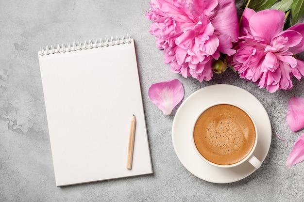 Gorąca kawa, kwiaty piwonii i notatnik