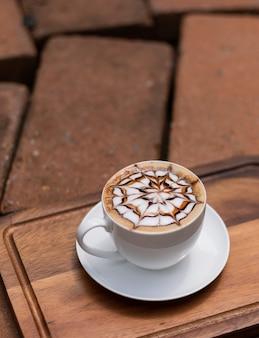 Gorąca kawa latte art na drewnianym stole, czas na relaks