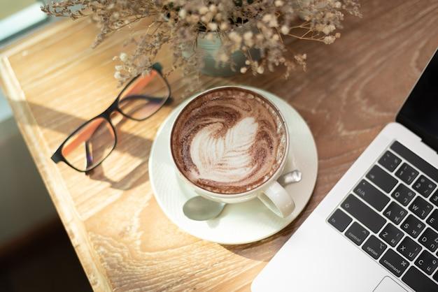 Gorąca kawa latte art, notes i szklanki na stół z drewna w kawiarni