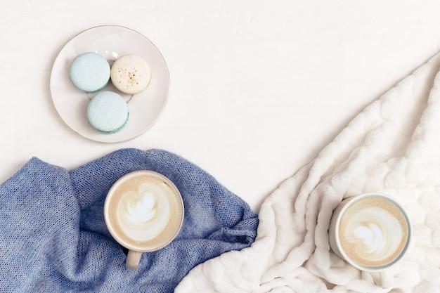 Gorąca kawa latte w dwóch dużych kubkach i słodkie makaroniki na betonowym stole z ciepłymi ubraniami z dzianiny