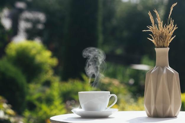 Gorąca kawa na stole na jesiennym tle