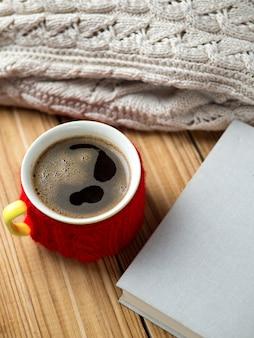 Gorąca kawa na stole z książką i ciepłym swetrem