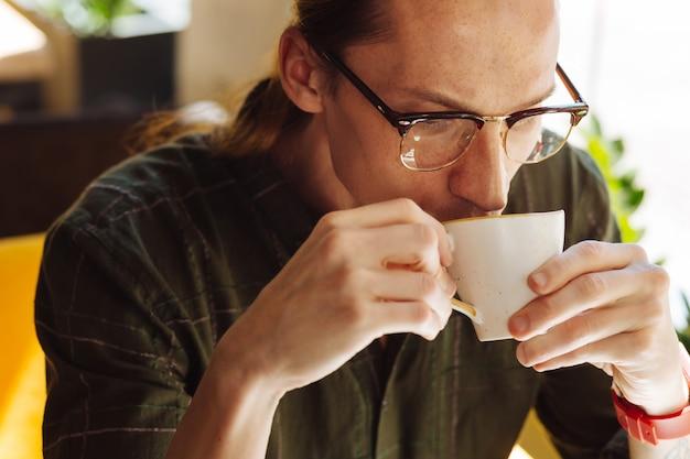 Gorąca kawa. portret dobrze wyglądającego młodego mężczyzny podczas picia kawy