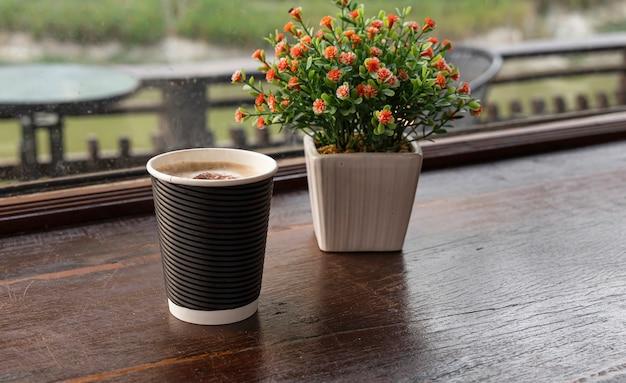 Gorąca kawa umieszczona jest na drewnianym stole z doniczką przy oknie.