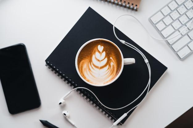 Gorąca kawa w filiżance przy biurku komputerowym