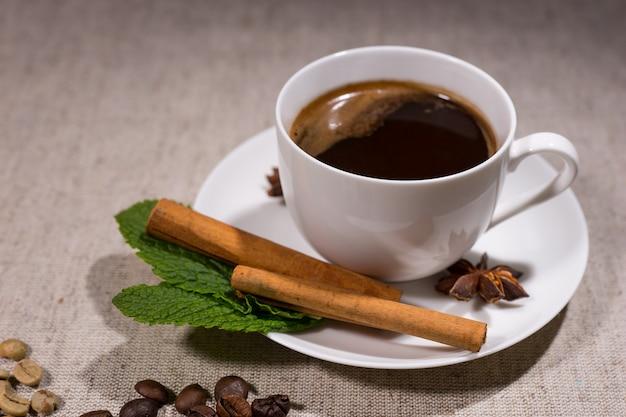 Gorąca kawa w filiżance z laskami cynamonu i miętą