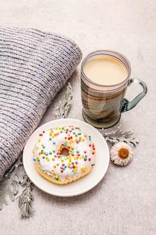 Gorąca kawa z pączkiem. zimowy napój dla dobrego nastroju ze swetrem, liśćmi i kwiatami.