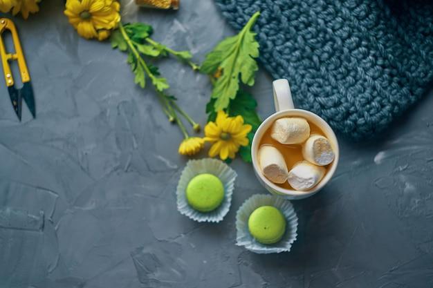 Gorąca kawa z pianką i mlekiem lub kremowe i zielone makaroniki na stole na poddaszu w romantycznym otoczeniu