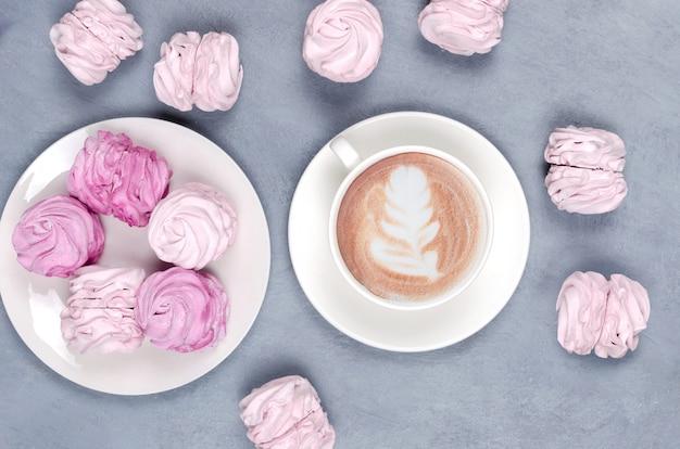 Gorąca kawa z różowym ptasie mleczko na szaro