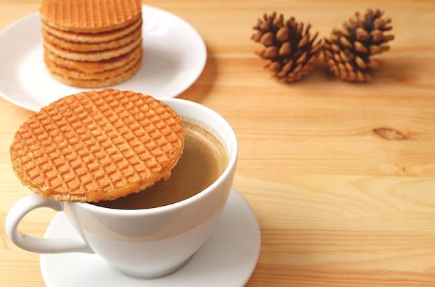Gorąca kawa ze stroopwafel umieszczona na szczycie filiżanki na drewnianym stole z suchymi szyszkami sosnowymi