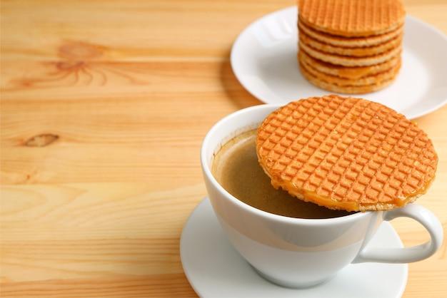 Gorąca kawa ze stroopwafelem umieszczona na górze filiżanki z rozmytym stosem stroopwafela w tle