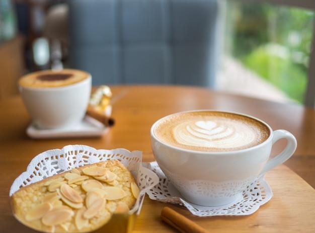 Gorąca kawa ze sztuką latte w białej filiżance z chlebkiem migdałowym umieszczona na drewnianym stole.