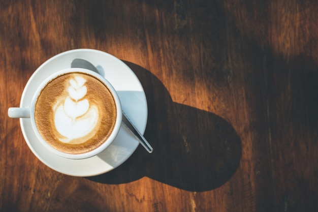 Gorąca latte kawa w białej filiżance na drewnianym stole z kopii przestrzenią dla teksta lub projekta