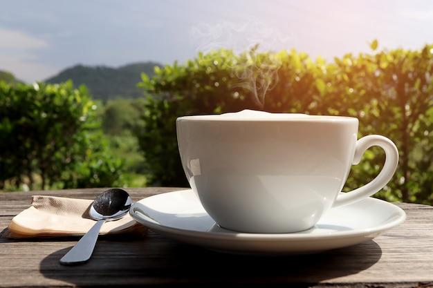 Gorąca latte świeża kawa w białej filiżance z mleko pianą i dymem na drewnianym stole.