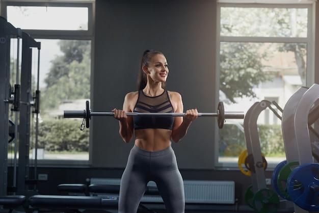 Gorąca młoda dziewczyna w siłowni przyczajony ze sztangą, przed sprzętem siłowni.