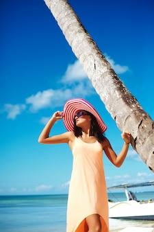 Gorąca piękna kobieta w kolorowe schowanko i sukienka spaceru w pobliżu plaży oceanu w gorący letni dzień w pobliżu dłoni