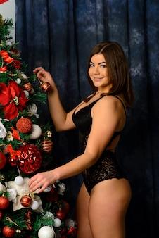 Gorąca piękna kobieta w koronkowej czarnej bieliźnie pozuje przy kominku. świąteczne wnętrze.