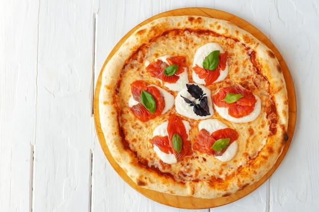 Gorąca pizza margherita na białym drewnianym stole