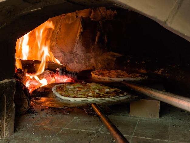 Gorąca pizza w piecu na węgiel drzewny z ogniem