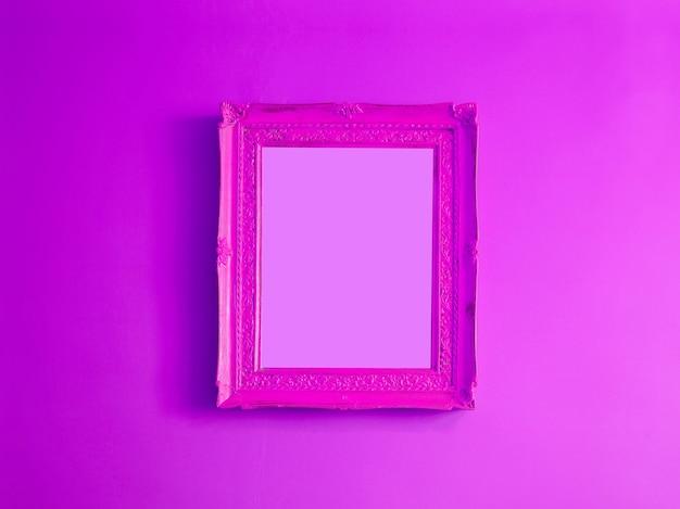 Gorąca różowa antyczna pusta ramka na zdjęcia wyizolowana na gradientowej fioletowej ścianie