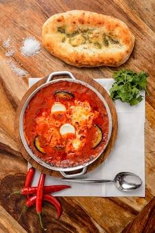 Gorąca shakshuka z pomidorami, jajkami i ziołami.