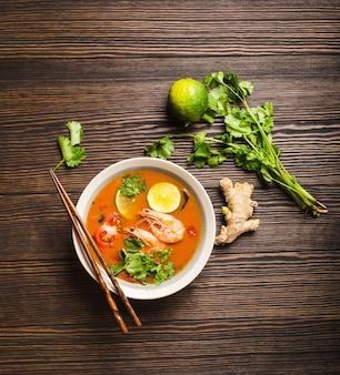 Gorąca, świeża, pikantna tradycyjna tajska zupa tom yum z krewetkami, limonką, kolendrą w misce na rustykalnym drewnianym tle