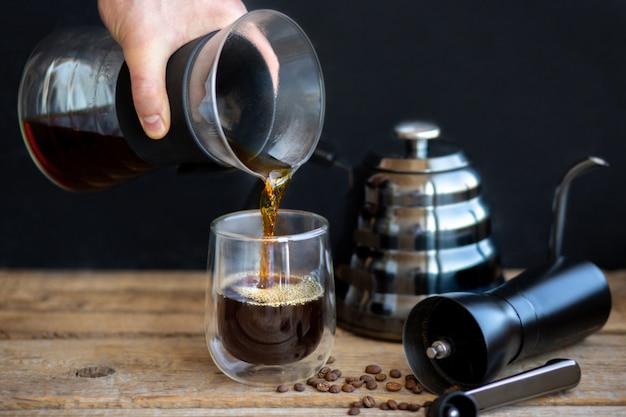 Gorąca szklanka nalewa się do szklanki. parzenie kawy przez lejek. filiżanka świeżego gorącego filtra. młynek z czajnikiem i ziarnami kawy. pachnący gorący napój. kawa parzona w domu. przerwa na kawę