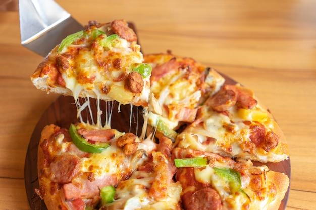 Gorąca taca do pizzy z dodatkami do pizzy zawiera szynkę, wieprzowinę, paprykę i warzywa, pizzę,