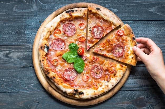 Gorąca włoska pizza na rustykalnym drewnianym stole.