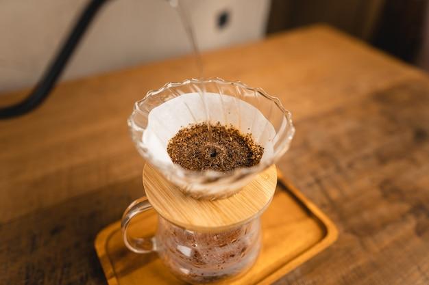 Gorącą wodę do zakraplacza do kawy nad szklanym słojem.