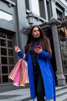 Gorąca wyprzedaż. piękna młoda kobieta moda z torby na zakupy w pobliżu okna sklepu dzwoniąc inteligentny telefon, stonowanych. zakupy kobieta zabawa telefon