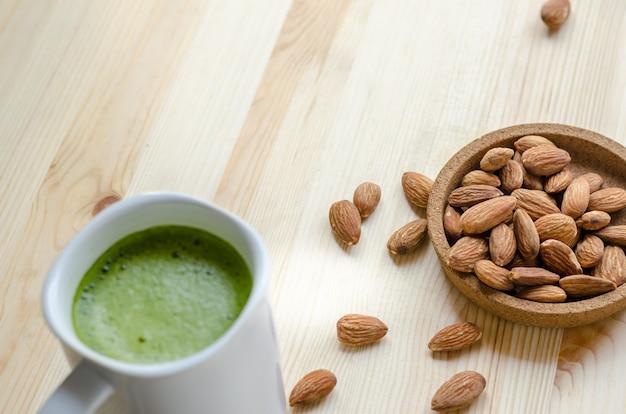 Gorąca zielona herbata latte w leniwym czasie z orzechami migdałów
