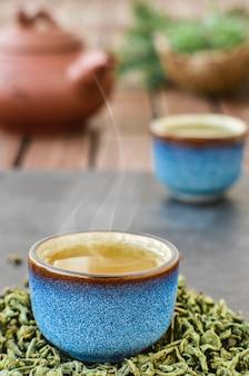 Gorąca zielona herbata w niebieskiej miseczce, kamienny stół. z miski unosi się para. liście herbaty obok filiżanki. zbliżenie, ceremonia parzenia herbaty. minimalny