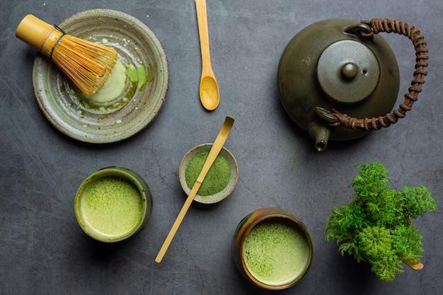 Gorąca zielona herbata w szklance ze śmietaną polaną zieloną herbatą, ozdobiona zieloną herbatą w proszku.