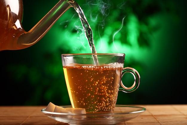 Gorąca zielona herbata w szklanym czajniku i filiżance