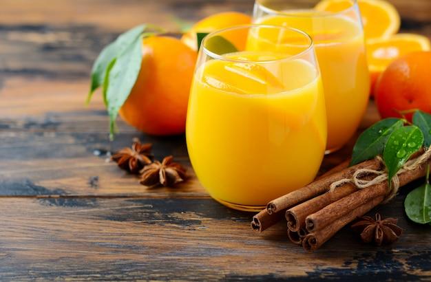 Gorąca zimowa koktajlowa pikantna pomarańczowa poncz z anyżkiem cynamonowym i goździkami.