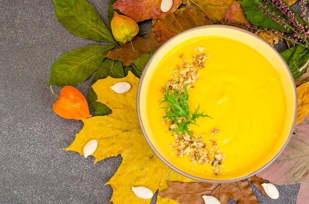 Gorąca zupa dyniowa z suszonych liści jesienią.