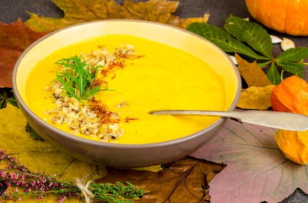 Gorąca zupa dyniowa z suszonymi jesiennymi liśćmi.